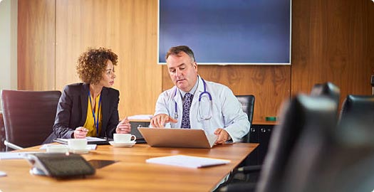 Image of two doctors meeting in a conference room.